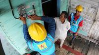 Karyawan PT PLN (Persero) tengah memasang meteran listrik di salah satu rumah warga Natuna, Kepulauan Riau. (Foto: Humas PLN)