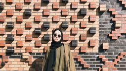 Wanita kelahiran 1992 ini mengenakan pashmina dan celana hitam yang dipadukan dengan sweater dan jaket coklat memberi kesan outfit santai dan simple. (Liputan6.com/IG/@gitasav)