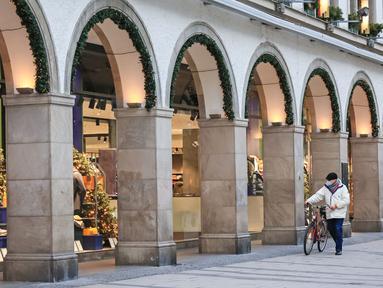 Pejalan kaki berjalan melewati etalase toko sembari menuntun sepeda di Munich, Jerman (11/12/2020). Kasus penularan dan kematian harian COVID-19 di Jerman terus meningkat dan mencapai rekor tertinggi baru pada Jumat (11/12), menurut data dari Robert Koch Institute (RKI). (Xinhua/Philippe Ruiz)