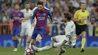 Lionel Messi mendapat adangan dari bek Real Madrid, Sergio Ramos dpada duel El Clasico di Santiago Bernabeu stadium, Madrid, Spanyol, Minggu, (23/4/2017). Barcelona menang 3-2.  (AP/Daniel Ochoa de Olza)
