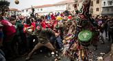 """Orang-orang melempari seorang pria berkostum ala setan dengan sayuran lobak selama Festival Jarramplas di kota Piornal, Spanyol, Sabtu (19/1). Sosok """"setan"""" itu disebut dengan Jarramplas yang dikenakan salah satu pemuda desa terpilih. (AP/Javier Fergo)"""