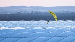 Seorang aktivis Greenpeace dengan menggunakan paraglider saat akan memasuki Stadion Allianz Arena, Muenchen. Belum bisa dipastikan aksi yang bisa dibilang berani tersebut ditujukan kepada pihak siapa. (Foto: AP/DPA/Matthias Balk)