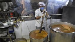 Relawan dari asosiasi Nass el-Khir memasak makanan untuk didistribusikan kepada mereka yang membutuhkan selama bulan suci Ramadan di Aljir, Aljazair, Senin (18/5/2020). (RYAD KRAMDI/AFP)