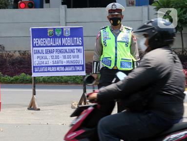 Polisi memberhentikan kendaraan saat pengendalian mobilitas ganjil genap untuk pengunjung TMII di Jalan Pintu 1 TMII, Jakarta, Sabtu (18/9/2021). Polda Metro Jaya memberlakukan pembatasan mobilitas warga dengan sistem ganjil genap pada TMII dan Taman Impian Jaya Ancol. (Liputan6.com/Herman Zakharia)