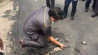 Anggota DPRD Muara Enim Sumatera Selatan (Sumsel) Yusran Effendi mengeruk aspal jalan yang sudah kering menggunakan tangan kosong (Dok. Instagram Muara Enim Terkini / Nefri Inge)