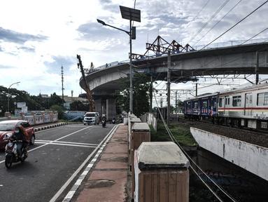 Kendaraan dan kereta Commuter Line saat melintas di bawah proyek jalur lintas atas (flyover) Cakung, Jakarta, Kamis (17/12/2020). Flyover dengan biaya pembangunan mencapai Rp 261 miliar ini diharapkan mampu mengatasi kemacetan yang kerap terjadi di kawasan tersebut. (merdeka.com/Iqbal Nugroho)