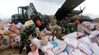 Prajurit TNI dibantu tentara Amerika Serikat mendistribusikan bantuan logistik yang tiba di Bandara Mutiara Sis Al-Jufri, Palu, Sulawesi Tengah, Minggu (7/10). Tentara AS membantu mendistribusikan dari landasan menuju bandara. (Liputan6.com/Fery Pradolo)