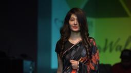 Seorang wanita bernama Reshma Qureshi berjalan diatas panggung saat peragaan busana di New Delhi, India (25/11). Reshma Qureshi  adalah wanita korban kekerasan dan penyiraman air keras yang kerap terjadi di India. (AFP Photo/Dominique Faget)