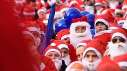 Peserta mengambil bagian dalam Santa's Fun Run di Riga, Latvia, Minggu (8/12/2019). Ini merupakan acara amal yang pesertanya bersenang-senang dengan berlari atau berjalan kaki sambil mengenakan kostum Sinterklas untuk mengumpulkan dana bagi anak-anak di rumah sakit Latvia. (Gints Ivuskans/AFP)