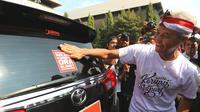 Gubernur Jawa Tengah Ganjar Pranowo menempelkan stiker antikorupsi di mobil dinas. (Dok.@Humasjateng)