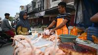 Pedagang memotong daging ayam saat melayani pembeli di sebuah pasar tradisional usai gempa dan tsunami melanda Palu, Sulawesi Tengah, Kamis (4/10). Pedagang mengaku memperdagangkan barangnya dengan harga standar. (Permata SAMAD/AFP)