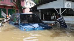 Warga melihat kondisi mobil yang terseret arus banjir di perumah Ciledug Indah, Tangerang, Banten, Kamis (2/1/2020). Sebelumnya, media sosial diramaikan dengan video sejumlah mobil yang terseret arus banjir hingga ratusan meter ke arah dalam perumahan Ciledug Indah. (Liputan6.com/Angga Yuniar)