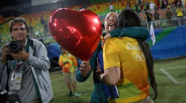 Atlet Rugby asal Brasil, Isadora Cerullo (kiri) memeluk kekasihnya, Marjorie Enya usai seremoni pemberian medali cabang olahraga rugby Olimpiade 2016 di Stadium Deodoro, Rio de Janeiro, Brasil, (8/8). (REUTERS/Alessandro Bianchi)
