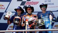 Pembalap Repsol Honda, Marc Marquez merayakan kemenangannya pada balapan MotoGP Amerika di samping Maverick Vinales dari Movistar Yamaha dan Andrea Iannone dari Suzuki Ecstar di podium Circuit of the Americas (COTA), Austin, Minggu (22/4). (AP/Eric Gay)