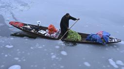 Seorang pria mengendarai sebuah kapal yang penuh dengan sayuran di dekat bagian beku danau Dal setelah hujan salju lebat di Srinagar (16/1/2020). Lapisan tipis es menutupi perairan Danau Dal di Srinagar. (AFP Photo/Tauseef Mustafa)