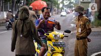 Petugas merazia warga yang tidak mengenakan masker di Kelurahan Cimone, Kota Tangerang, Banten, Rabu (15/7/2020). Guna memberi efek jera, Pemkot Tangerang memberlakukan sanksi sosial kepada pelanggar PSBB seperti menyapu dengan memakai rompi bertulis 'Pelanggar PSBB'. (Liputan6.com/Angga Yuniar)