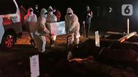 Petugas pemakaman mengenakan hazmat saat membawa jenazah pasien COVID-19 untuk dimakamkan di TPU Pondok Ranggon, Jakarta, Selasa (14/7/2020). Hingga hari ini, lima provinsi mencatat tambahan kasus baru tertinggi yakni Jatim, DKI Jakarta, Sulsel, Kalsel, dan Sumut. (Liputan6.com/Herman Zakharia)