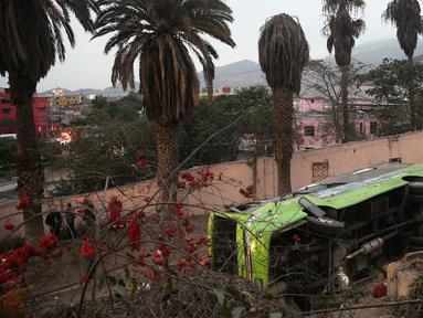 Sebuah bus wisata setelah mengalami kecelakaan di Lima, Peru, (9/10). Menurut petugas pemadam kebakaran, sedikitnya tujuh orang tewas setelah  bus wisata tersebut keluar jalur saat turun bukit di distrik Rimac. (AFP Photo/Andina/Ho)