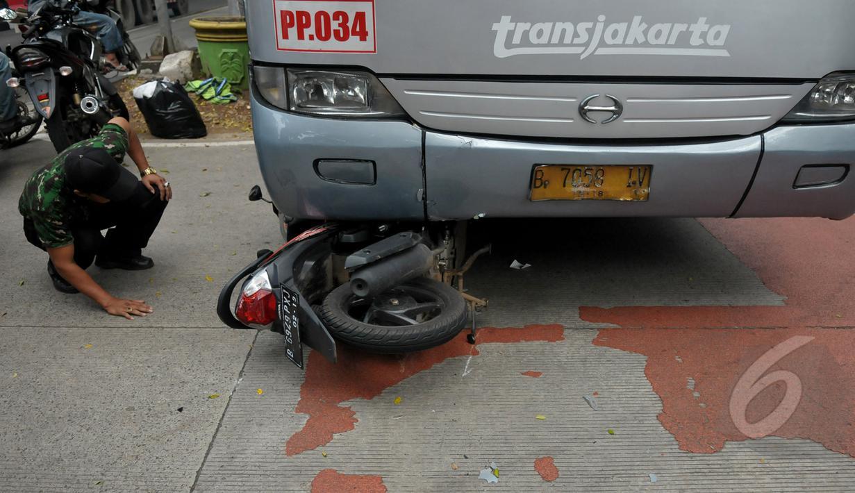 Bus Transjakarta bernomer polisi B 7058 IV menabrak pengendara sepeda motor di kawasan permata hijau, Jakarta, Jumat (27/3/2015). Sejumlah warga sedang melakukan evakuasi speda motor yang berada di dalam bus transjakarta. (Liputan6.com/Johan Tallo)