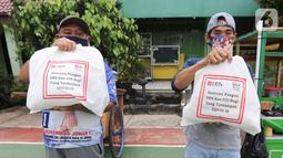 Warga terdampak Covid-19 menunjukkan paket makanan yang diterima di Cipulir, Jakarta Jumat (18/12/2020). Bantuan yang diberikan kepada pekerja sektor informal menjadikan total donasi yang diberikan DBS Group untuk Indonesia sebesar IDR27,2 miliar. (Liputan6.com/Fery Pradolo)