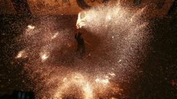 Seorang pemuda Palestina bermain-main dengan kembang api buatan sendiri ketika malam bulan suci Ramadan di kamp pengungsi Rafah, Jalur Gaza selatan, Senin (4/5/2020). Atraksi kembang api ini sedianya dilakukan setiap kedatangan bulan suci Ramadan. (Photo by MAHMUD HAMS / AFP)