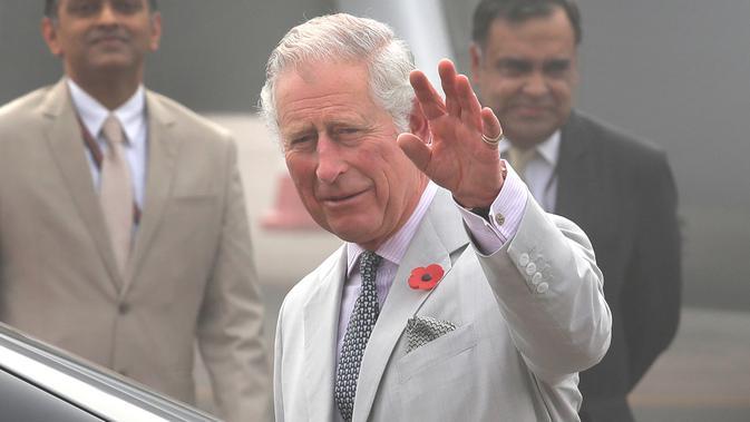 Pangeran Charles melambaikan tangan ke arah awak media setibanya bersama sang istri, Camilla di New Delhi yang diselimuti kabut asap, Rabu (8/11). Kabut asap tebal akibat polusi udara yang tinggi menyelimuti India. (AP Photo/Manish Swarup)