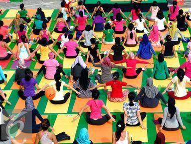 "Sejumlah peserta mengikuti gerakan Yoga in the Air di rooftop Plaza Semanggi, Jakarta, Sabtu (30/4). Kegiatan ini dilakukan sebagai bentuk kampanye ""Stay fresh and healthy with Kiranti"".(Liputan6.com/Johan Tallo)"