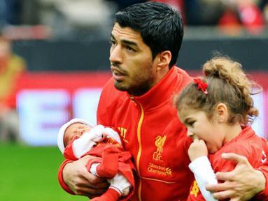 Striker Liverpool Luis Suarez membawa kedua putrinya menjelang pertandingan sepak bola Liga Inggris antara Liverpool vs Crystal Palace di stadion Anfield (05/10/13). (AFP/Paul Ellis)