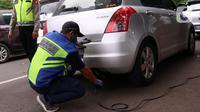 Petugas memeriksa emisi mobil di Jakarta Barat, Rabu (13/1/2021). Dinas Lingkungan Hidup DKI Jakarta mengumumkan kendaraan yang tidak mengikuti uji emisi atau tidak lulus uji emisi gas buang akan dikenakan disinsentif tarif parkir yang tinggi dan tilang. (Liputan6.com/Angga Yuniar)