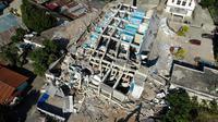 Petugas membersihkan puing-puing dari hotel Roa Roa yang runtuh di Palu, Sulawesi Tengah, Senin (1/10). Jumlah korban tewas akibat gempa dan tsunami yang melanda Palu dan Donggala diperkirakan akan meningkat. (JEWEL SAMAD/AFP)