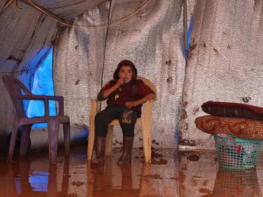 Seorang anak duduk dalam tendanya yang kebanjiran di Kamp Cordoba, Batabu, Idlib, Suriah, Rabu (16/1). Hujan badai membuat kamp pengungsian mereka kebanjiran. (Aaref Watad/AFP)