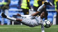 Putra dari Cristiano Ronaldo melakukan tendangan salto saat menemani sang ayah di Stadion Santiago Bernabeu, Madrid, Minggu (8/4/2018). Tendangan ini mirip seperti saat CR 7 membobol gawang Juventus. (AFP/Gabriel Bouys).