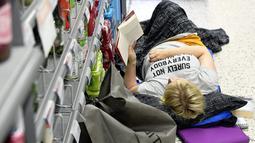 Seorang wanita membaca buku di atas kasur dekat rak minuman di sebuah toko kelontong saat gelombang panas melanda Helsinki di Finlandia, 4 Agustus 2018. Para pelanggan mendatangi toko ber-AC ini untuk menginap. (Heikki Saukkomaa/Lehtikuva /AFP)