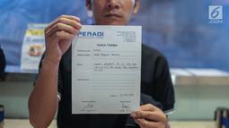Mantan terpidana mati kasus pembunuhan Yusman Telaumbanua menunjukkan surat tanda terima usai pertemuan tertutup dengan pihak kontras terkait pelaporan mantan penasihat hukum Yusman di Kantor Peradi, Jakarta, Rabu (21/11).  (Liputan6.com/Faizal Fanani)