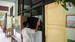 Petugas mengelap kaca di SD Negeri Kota Bambu 03/04, Jakarta, Sabtu (21/11/2020). Pemerintah pusat memberikan kewenangan pemerintah daerah membuka sekolah dan melakukan pembelajaran tatap muka pada semester genap tahun ajaran 2020/2021. (Liputan6.com/Faizal Fanani)