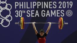 Lifter Aisyah Windy melakukan angkatan saat SEA Games 2019 cabang angkat besi nomor 49 kg di Stadion Rizal Memorial, Manila, Minggu (1/12). Dirinya meraih emas dengan total angkatan 104 kg. (Bola.com/M Iqbal Ichsan)