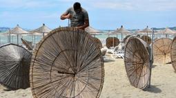Seorang pekerja memperbaiki payung jerami di sebuah pantai di Qerret, dekat kota Kavaja, Albania pada 1 Juni 2020. Rencananya pada 6 Juni mendatang, semua pantai umum akan dibuka untuk wisatawan setelah Albania menerapkan langkah-langkah pelonggaran pencegahan virus corona. (SHKULLAKU / AFP)