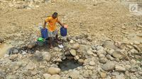 Warga mengambil air pada lubang di aliran Sungai Cipamingkis yang kering, Cibarusah, Bekasi, Jabar, Kamis (2/8). Dua bulan tak diguyur hujan menyebabkan warga perbatasan Bogor-Bekasi dilanda kekeringan dan kesulitan air bersih. (Merdeka.com/Arie Basuki)