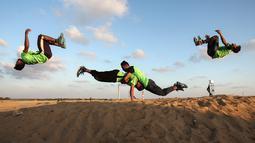 Empat pemuda Palestina melakukan aksi keterampilan parkour di dekat tenda warga di perbatasan Gaza, Palestina (10/4). Sebelumnya sejumlah warga membangun tenda di perbatasan Gaza untuk meminta hak tanah mereka atas Isreal. (AFP Photo/Said Khatib)