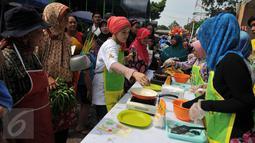 Sejumlah ibu-ibu melihat juru masak membuat jajanan tradisional di Pasar Pondok Labu, Jakarta Selatan (10/09). Acara yang diusung Gulaku untuk melestarikan jajanan tradisional Indonesia. (Liputan6.com/Gempur M Surya).