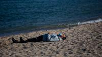Seorang pria mengenakan masker beristirahat ketika penguncian untuk memerangi penyebaran virus corona berlanjut di sebuah pantai di Badalona, dekat Barcelona, Spanyol, Selasa, (28/4/2020). (AP Photo/Emilio Morenatti)