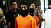 Pembunuh anak kandung di Pekanbaru digiring polisi untuk dibawa ke rumah sakit jiwa. (Liputan6.com/M Syukur)