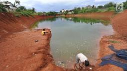 Anak-anak memancing pada bagian proyek pembangunan tol Cinere-Serpong yang berubah menjadi danau sedalam 4 meter di kawasan Cipayung, Tangsel, Banten (17/1). Pembangunan jalan Tol ini sepanjang 10,14 kilometer. (Merdeka.com/Arie Basuki)