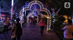 Pengunjung berfoto dengan dekorasi Natal menghiasi mal Central Park, Jakarta, Rabu (11/12/2019). Sejumlah pusat perbelanjaan di Jakarta mulai memasang dekorasi Natal untuk menarik minat pengunjung agar datang dan berbelanja. (Liputan6.com/Johan Tallo)
