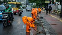 Petugas Dinas Kebersihan membersihkan genangan air usai hujan di kawasan jalan Sudirman, Jakarta, Rabu (22/11). Buruknya sistem drainase membuat petugas membersihkan genangan setiap kali hujan, meski dengan peralatan seadanya. (Liputan6.com/Faizal Fanani)