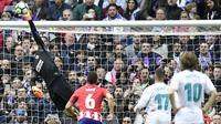 Kiper Atletico Madrid, Jan Oblak, mengamankan gawangnya dari tendangan pemain Real Madrid pada laga La Liga Spanyol di Stadion Santiago Bernabeu, Madrid, Minggu (8/4/2018). Kedua klub bermain imbang 1-1. (AFP/Javier Soriano)