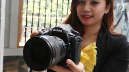 Seorang model berpose sambil menunjukkan kameran Nikon D850 saat peluncuran di Jakarta, Senin (29/1). Keunggulan lain kamera ini adalah sistem 153-point AF, selain itu bisa merekam video full frame dengan kualitas 4K UHD. (Liputan6.com/Angga Yuniar)
