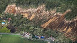 Pemandangan tanah longsor setelah gempa mengguncang Kota Atsuma, Prefektur Hokkaido, Jepang, Kamis (6/9). Gempa menghancurkan sejumlah rumah dan merobohkan tiang listrik. (Kyodo News via AP)
