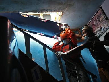 Relawan dan keluarga menurunkan jenazah warga untuk dievakuasi saat banjir melanda kawasan Cipinang Melayu, Jakarta Timur, Jumat (19/2/2021). Seorang nenek (80) meninggal di kediamannya, di lokasi banjir, di RW 04, kawasan tersebut karena sakit dan sudah lanjut usia. (Liputan6.com/Herman Zakharia)