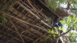 Seorang pria duduk di atas rumah pohon di desa Taik Kyi, Myanmar, 14 Januari 2016. Warga di desa ini terpaksa membuat rumah pohon untuk tempat berlindung dari kawanan gajah liar yang belakangan ini kerap menyerang desa Taik Kyi. (AFP PHOTO/Ye Aung THU)